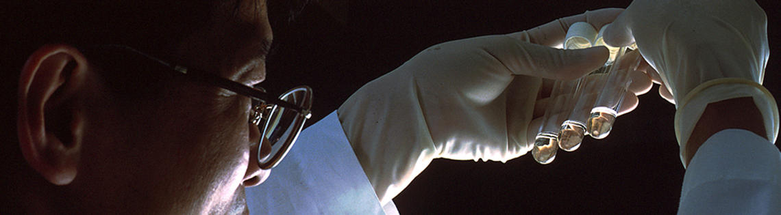 An NCI scientist in white lab coat and gloves holds up 3 test tubes.