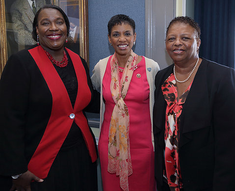 Three women stand next to each other