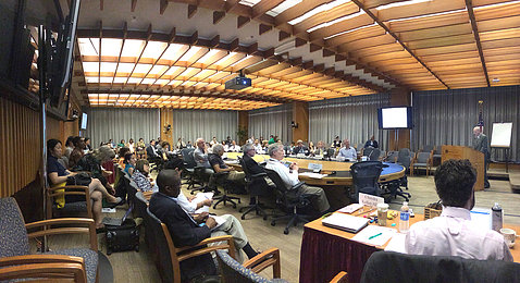 Workshop participants gather in conference room.