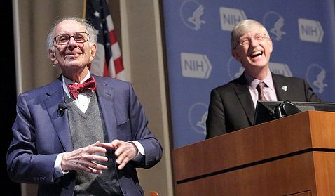 Dr. Kandel smiles on stage as a grinning Dr. Collins looks toward audience in Masur auditorium