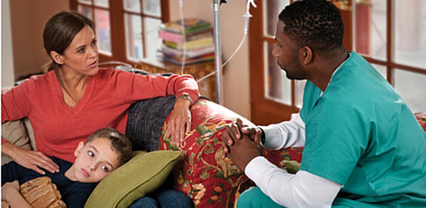 A mom, while son lays on her lap, talks with a doctor in her home.