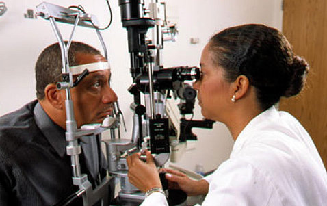 A man rests his chin on a diagnostic machine as optometrist examines his eyes.