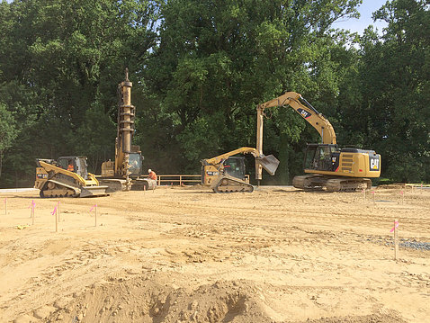 Construction site with drill and backhoe in background