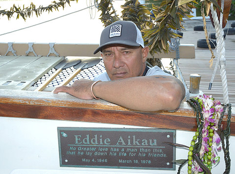 Kalepa rests his arm on edge of canoe, above plaque dedicated to the memory of Eddie Aikau