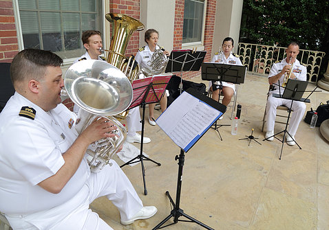 Musicians in their white uniforms play their brass instruments.