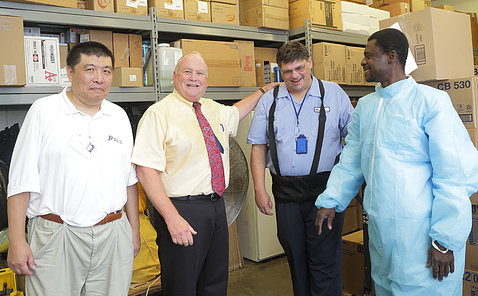 Wu, Weichbrod, White and Owusu with warehouse shelves and boxes behind them