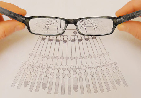 Eyeglasses magnify shapes on a chart.