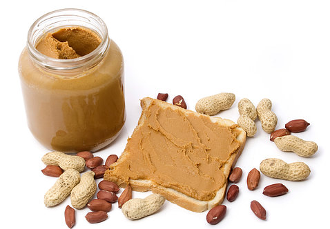 A jar of peanut butter sits on table next to slice of bread slathered with peanut butter as well as peanuts and shells.