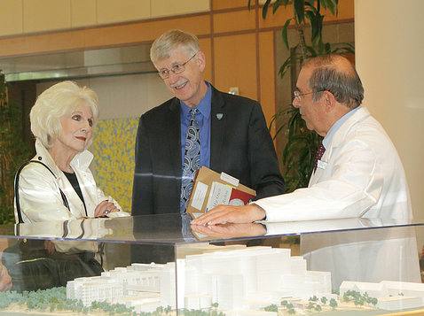 Rehm, Collins and Gallin talk next to CC model in the hospital atrium