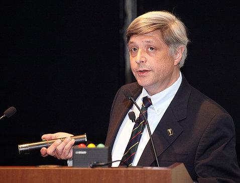 Dr. Jeffery Taubenberger holds laser pointer, speaking at podium