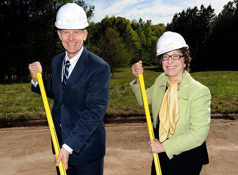 Wheeland and Birnbaum, wearing white hard hats, smile, holding shovels.
