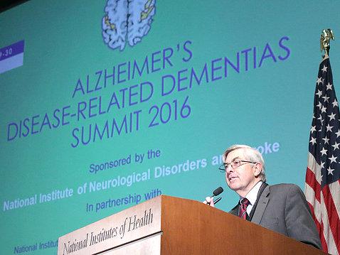 Koroshetz speaks from podium with summit title slide projected beside him.
