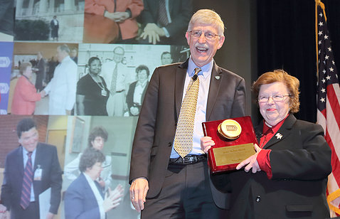 Plaque featuring a golden Petri dish is presented to Mikulski by Collins.