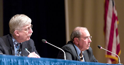 Seated at a panel table on stage, Collins and Gallin listen to people in the audience.