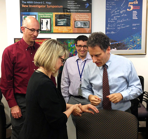Dr. Mark Prausnitz and colleagues watch Jill Heemskerk try on the microneedle patch.