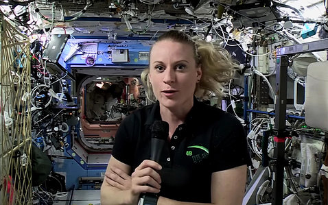 Dr. Kate Rubins talks into microphone inside space station, surrounded by wires and equipment.