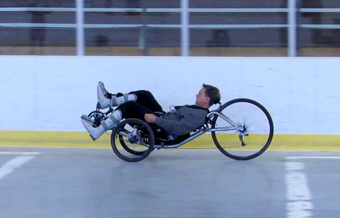 Mark Muhn rides around a track on a NIBIB-created tech-assisted three-wheeled cycle.