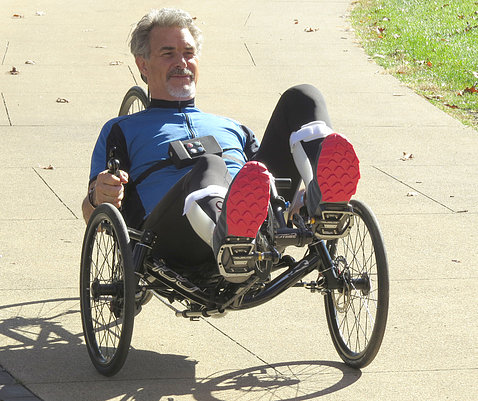 Michael McClellan rides on a tech-assisted three-wheeled recumbent cycle.