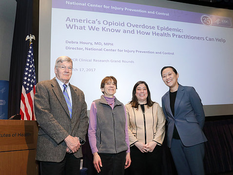 Four people gather for photo in front of title slide