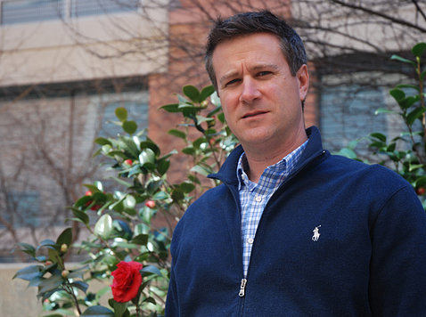 Hartz poses in front of rose bush in garden outside the Clinical Center