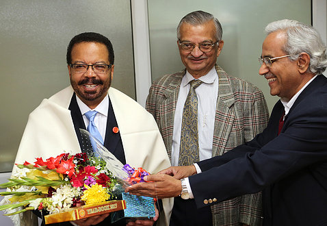 A smiling Pettigrew holds yearbook and bouquet of flowers, flanked by Kakodkar, and Tyagi