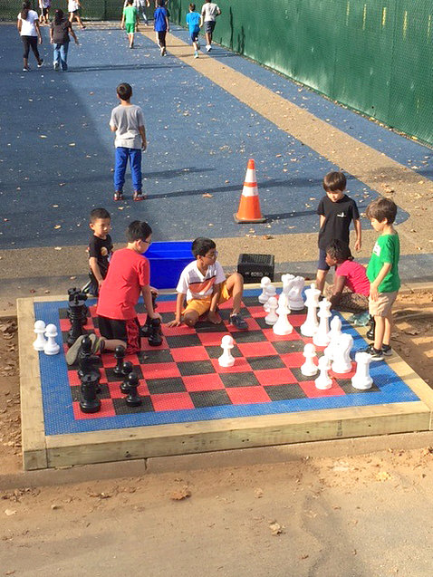 Children play on top of life-size, outdoor chess board