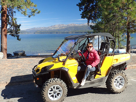Haynes in dune buggy with lake behind her.