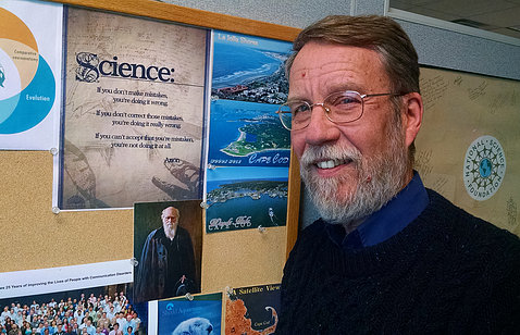 Dr. Christopher Platt stands in front of bulletin board with science posters.