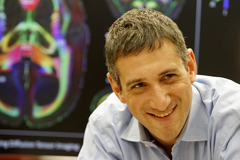 Reich smiles in front of a colorful MRI brain image