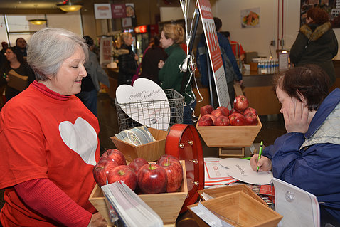 Woman in red heart sweatshirt stands behind table display of red apples as visitor looks on.