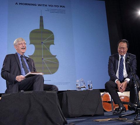 Collins sits on stage with Yo-Yo Ma