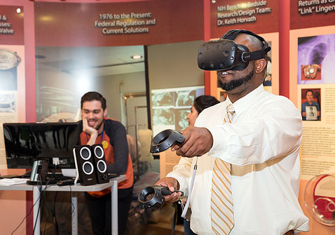 A man holds out, moves handheld device and wears head gear to try virtual reality experience in Clinical Center south lobby.