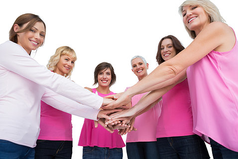 Six women wearing pink stack their hands together in unity