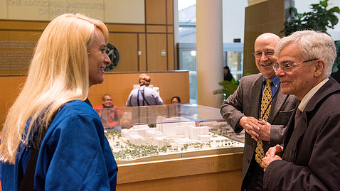 Gilman and Gottesman, standing next to Clinical Center model in the CC atrium, talk with Rubins