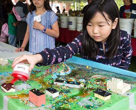 At Earth Day event outside, 7-year-old Hanna Cho examines green model of a town, pouring beads representing trash from a container to learn effects of pollution.