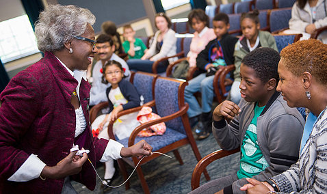 Dr. Valantine holds a catheter wire while talking with students in Wilson Hall.