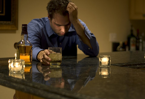 A man sits at kitchen counter, forlorn, holding his head in one hand and a glass of whiskey in the other