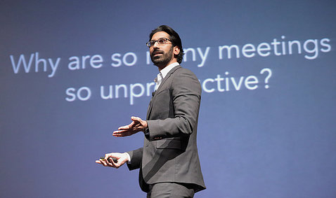 "Pittampalli speaks in front of a slide that asks ""Why are many meeting so unproductive?"""