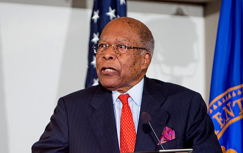 Former HHS secretary Dr. Louis Sullivan stands speaking in front of US flag