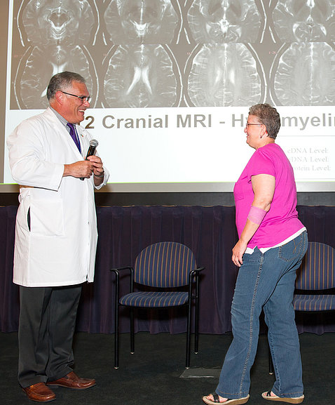 Standing,Toro speaks with patient Kelley on stage