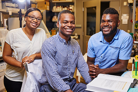 Three young people smile with a lab behind them