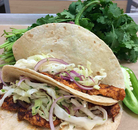 Two soft tacos filled with fish and onions sit on a bed of lettuce.