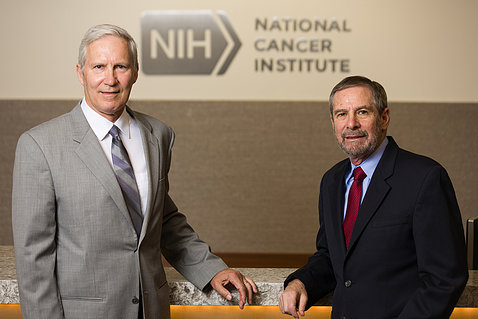 Schiller, Lowy stand in front of National Cancer Institute sign