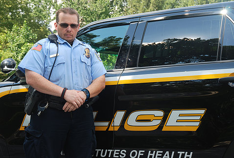 Corporal McKee stands in front of police cruiser.