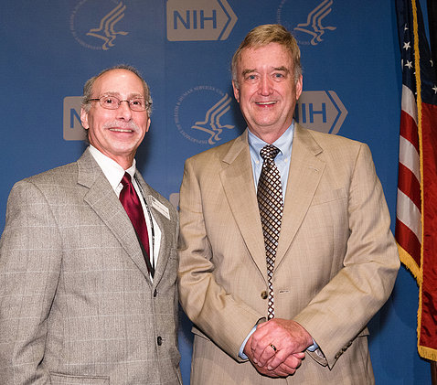 Dr. Robert Lembo and Sullivan pose together in front of blue NIH backdrop.
