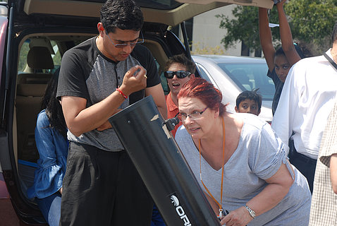 Iyer helps a woman use a telescope