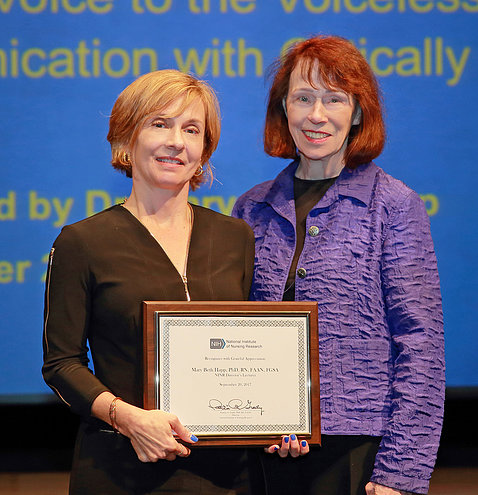 Dr. Mary Beth Happ holds plaque, poses with Dr. Grady