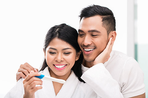 Woman smiling, holding pregnancy test results with man smiling over her shoulder