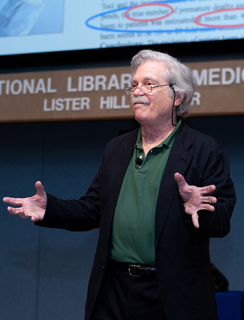 Dr. Alan Kay gestures with hands at NLM lecture.