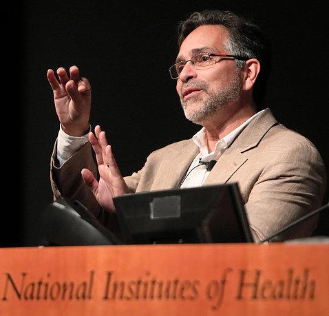 Dr. Alejandro Sánchez Alvarado motions with hands at the podium